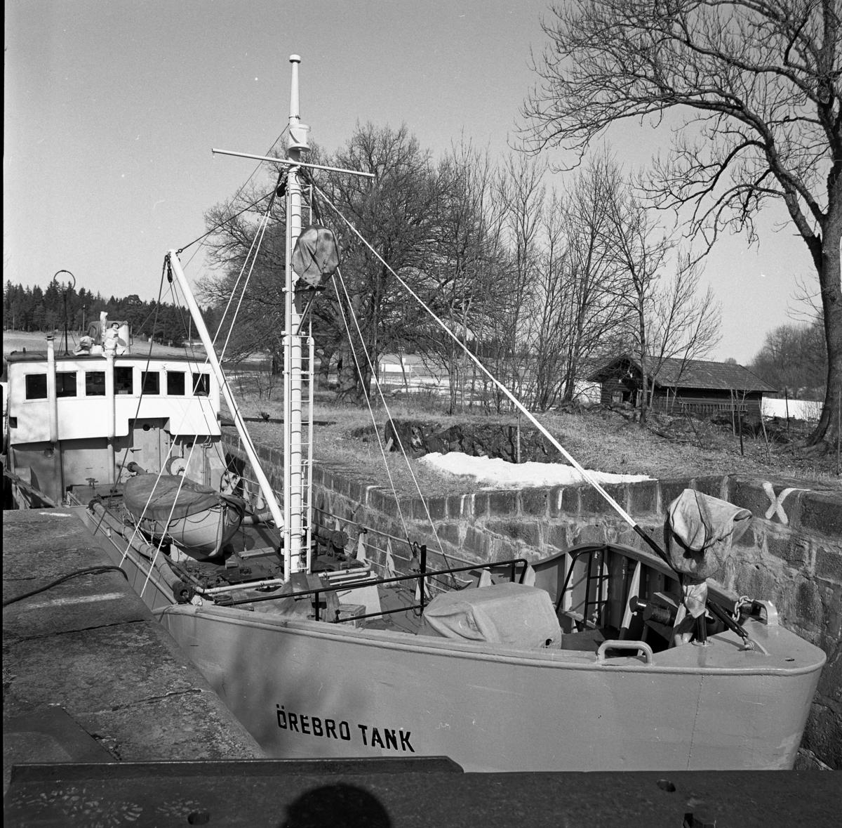"""En stor tankbåt slussar in i Hjälmare kanal vid Gravudden. Det står """"Örebro tank"""" i fören. Det är vårvinter, snön ligger fläckvis kvar."""
