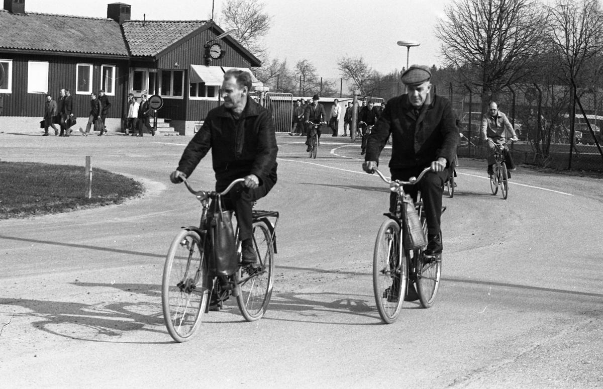 """Arbetsdagen är slut på CVA, Centrala Verkstaden Arboga. Två män kommer cyklande med matkassen på styret. I bakgrunden passerar folk genom grinden på väg till bilparkeringen eller busshållplatsen. Byggnaden, till vänster, kallas """"vakten"""", för där inne sitter vaktpersonalen."""