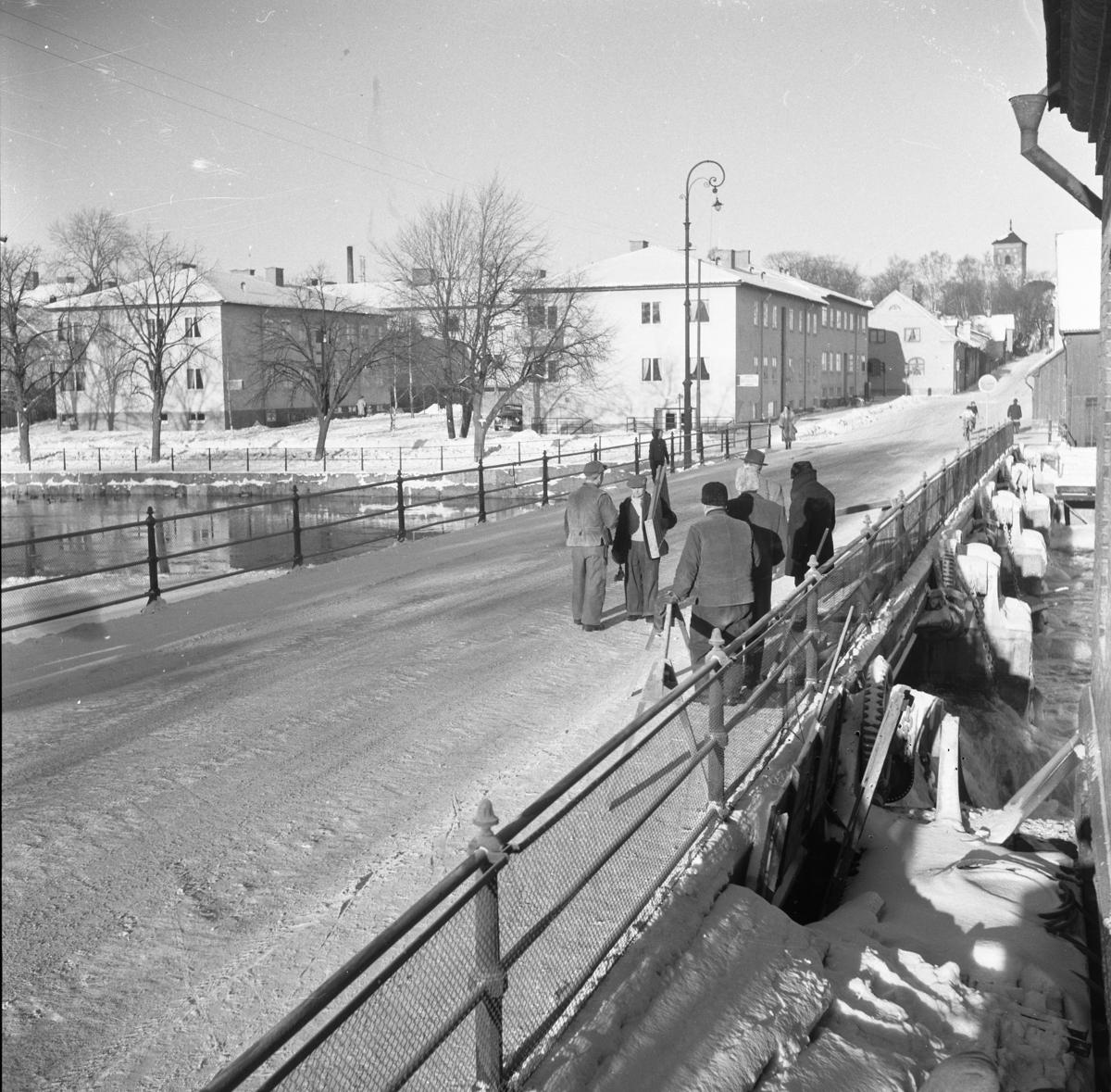 Män som samtalar på Herrgårdsbron. Två bockar är uppställda och en man bär en stege, de har arbete att utföra. Två av männen bär storvästar. Några andra har krimmelmössor. Två personer cyklar. En kvinna i päls är på väg över bron. Herrgårdsvägen, riktning Sankt Nikolai kyrka/ Nicolai kyrka. Fastigheter vid Strandvägen. Till höger anas magasinet tillhörande Arboga Kvarn och Maltfabrik. Två av männen bär storvästar. Några andra har krimmelmössor. Det är vinter och snö. Det är vinter och snö.