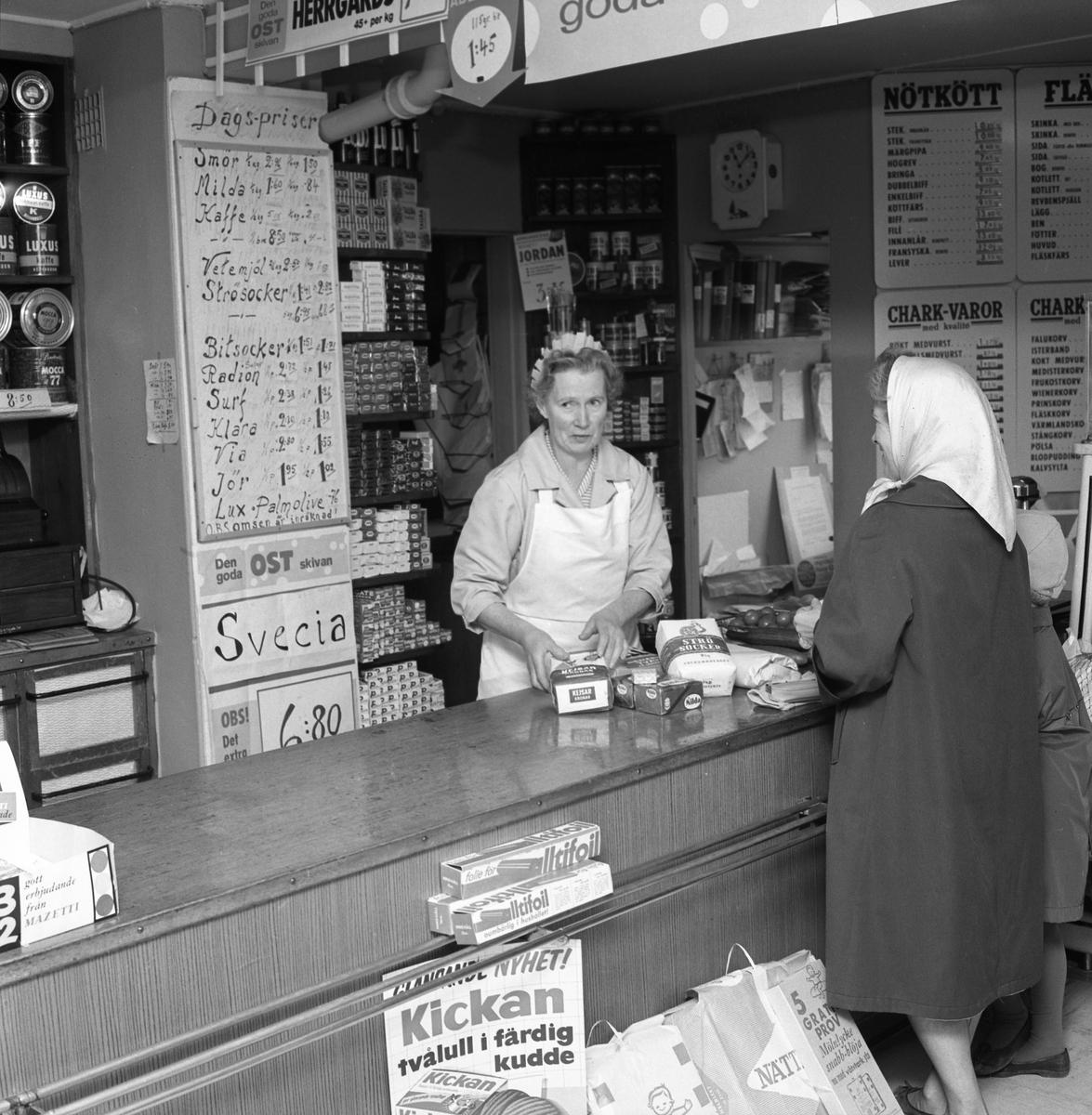 Yngve Anderssons speceriaffär på Hamrevägen. En kvinna köper varor över disk i handelsboden. Expediten är klädd i förkläde. Prislistor på väggen. Lanthandel, handelsbod