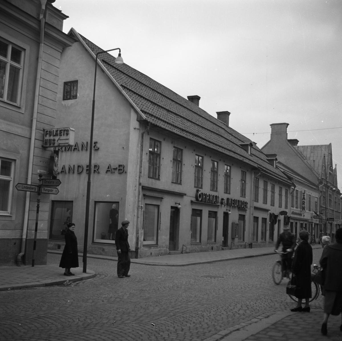 Öhrman & Melanders butik på Nygatan firar 50-årsjubileum. I skyltfönstret ses en skyltdocka. Affären säljer kläder.  Folkliv på gatan; människor promenerar och cyklar. Järnaffären ses en bit bort.
