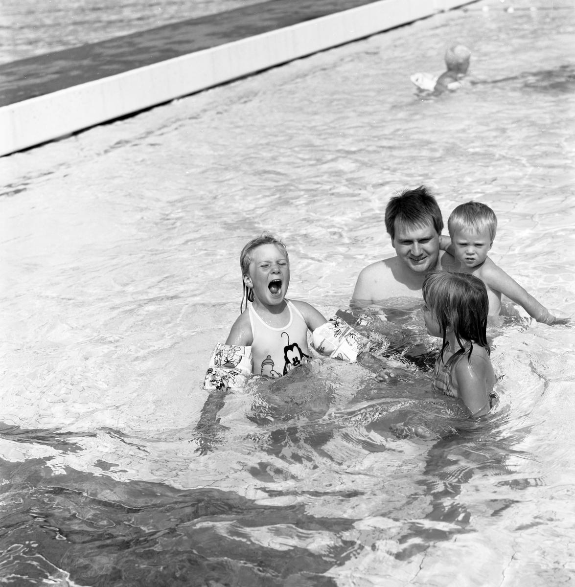 Familjen Sjöberg badar i utomhusbassängen på Ekbacksbadet. Pappa Leif Sjöberg har Simon Sjöberg på armen. Dottern Sara Sjöberg till vänster. Okänd flicka framför familjen.