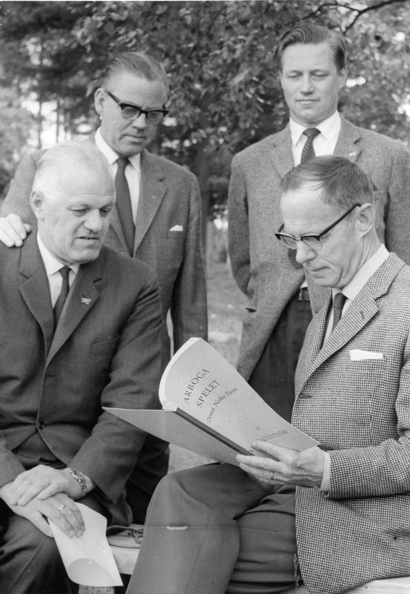 """Fyra kostymklädda män är samlade runt manuset till """"Giv oss fred"""". """"Giv oss fred"""", även kallat """"Arbogaspelet"""", är ett teaterstycke skrivet av Rune Lindström 1961. Handlingen, som är inspirerad av Arbogas klosterhistoria, är förlagt till början av 1500-talet. Uruppförandet skedde den 11 augusti 1962 och Rune Lindström spelade Engelbrekt Gertsson. Lions Club i Arboga stod för arrangemanget. Föreställningarna regnade bort och det blev ett stort ekonomiskt bakslag för föreningen. Spelet har framförts igen; 1987, 1988, 2012 och 2015 av medlemmar i """"Bygdespelets Vänner""""."""