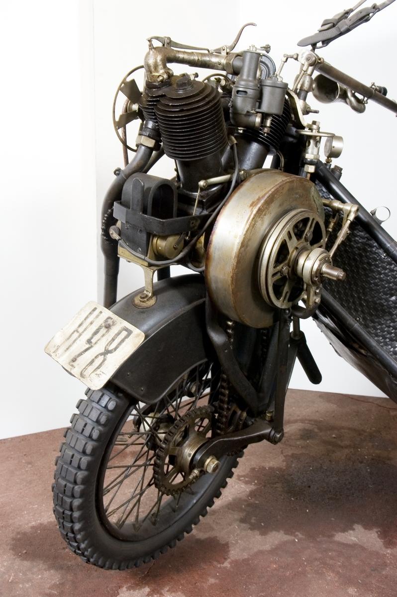 Trehjulig personbil för en passagerare med motorn monterad ovanför framhjulet som drivs med kedja. Motorn startas med vev och tändning sker med magnetapparat. Broms på framhjulet och ett bakhjul. Alla reglage sitter på styrstången. Registrerad 1914 som A3075, från1916 som H28.  Tvåcylindrig luftkyld bensinmotor, cylindervolym 880 cc Effekt 8 hk Två växlar framåt, ingen backväxel Högsta fart cirka 50 km/tim