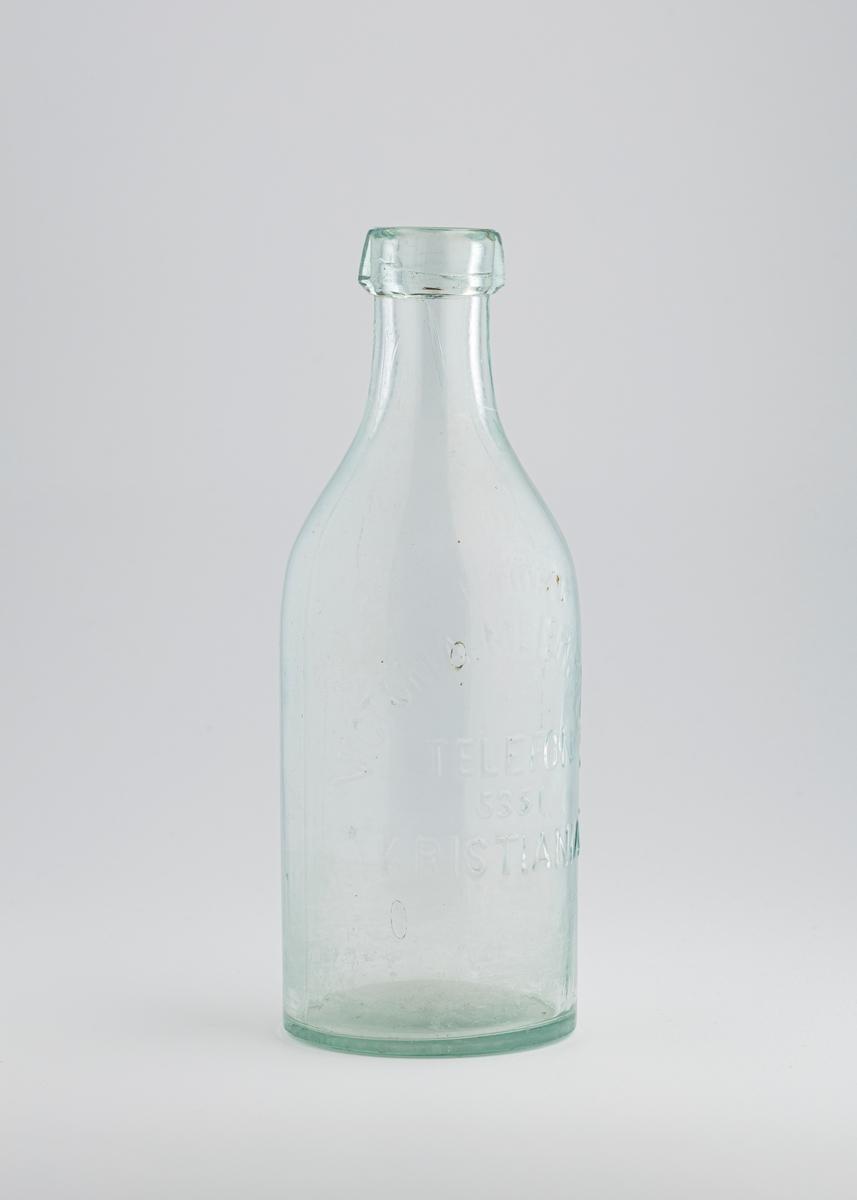 Liters melkeflaske som er høy og vid, og har et stort tut med kraftig kant rundt.
