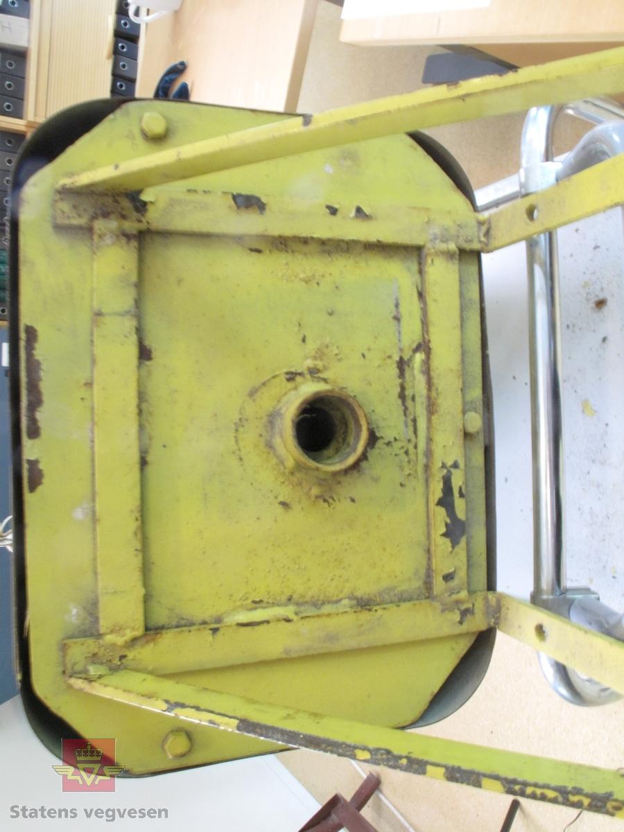 Gult bensinskap med håndpumpe. Pumpen kan tas ut, og kobles til et bensinfat. Pumpen er en stang som drives opp og ned. Det følger med to nøkler til å låse opp skapet. Malingen er delvis flasset av.
