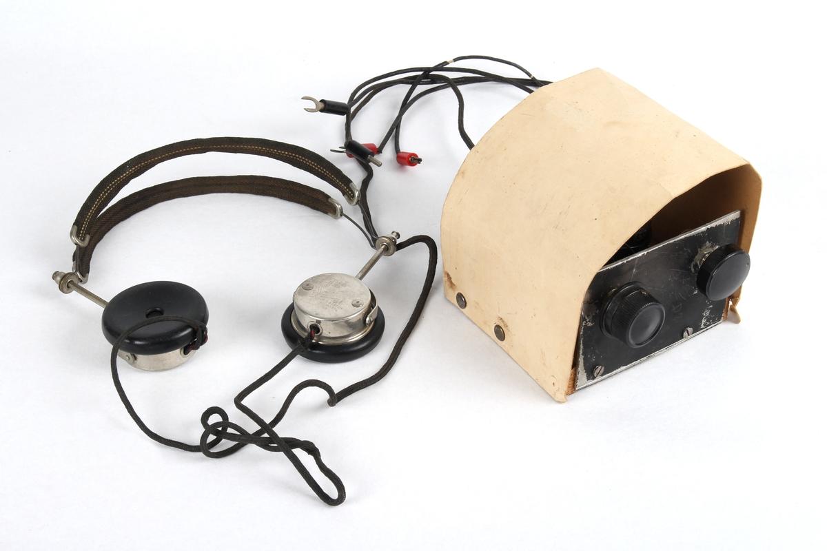 Hjemmelaget radio med tilhørende hodetelefoner. Laget i Haugesund og var brukt til radiolytting under andreverdenskrig