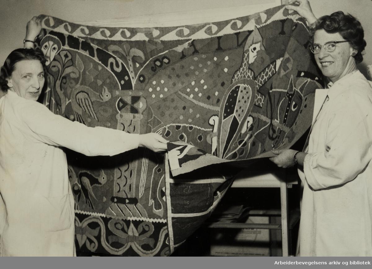 Kunstindustrimuseet. Baldisholteppet som er 800 år gammelt vises fram av tekstilkonservator Elsa Tharaldsen og assistent Liv Grosvold. Mars 1958