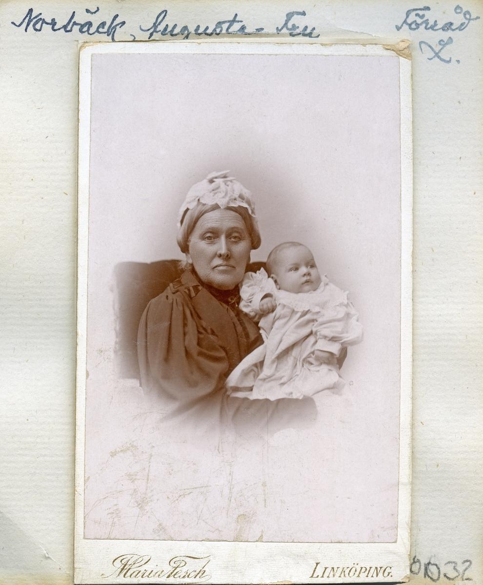 Porträtt av änkefru Augusta Norbeck, född Billing. I knät sitter hennes sonsonson Axel, född 1896. Augusta var född i Stockholm 1819 och från 1841 gift med kapten Axel Norbeck. Makarna ägde Förråd säteri i Östra Skrukeby socken. Hon blev änka redan 1858.