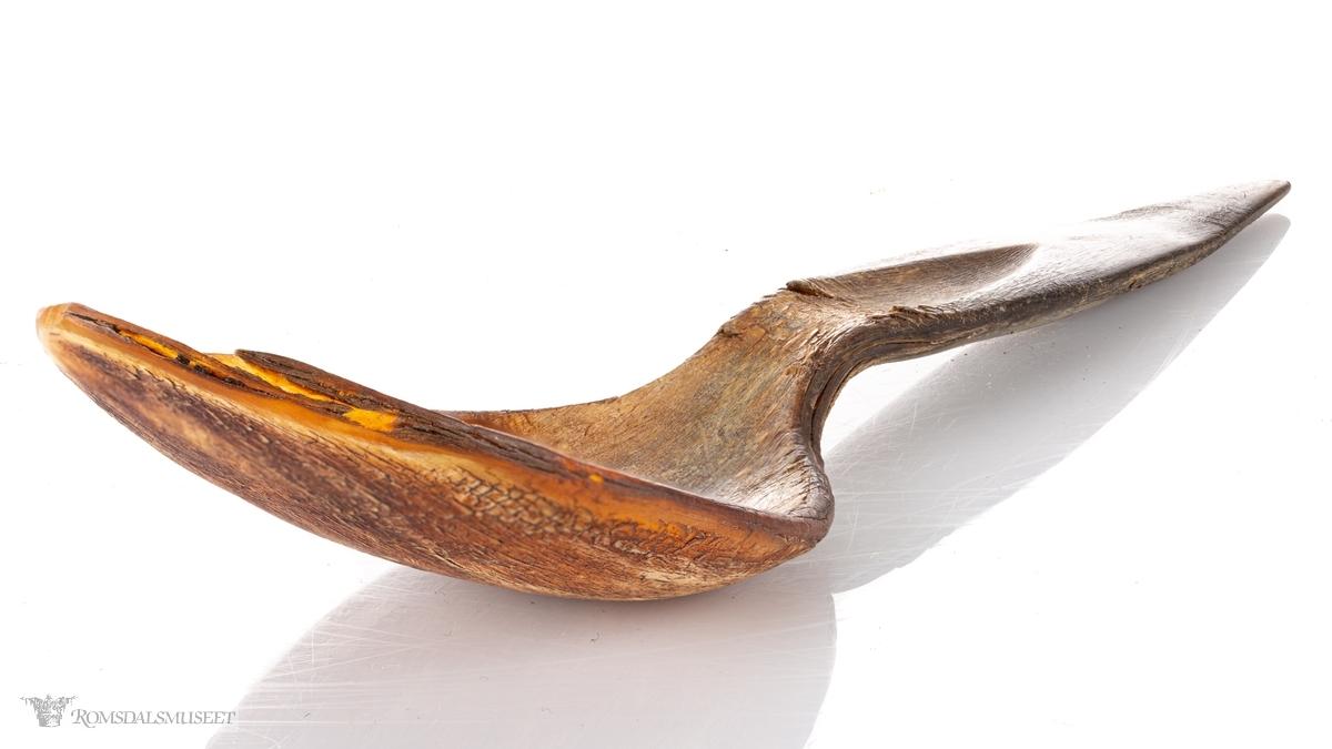 Skje av presset horn med bredt ovalt skjeblad som er spisset i endenSkaftet har et skåret spor fra bladet og midt opp på skaftet som ender i en spiss.