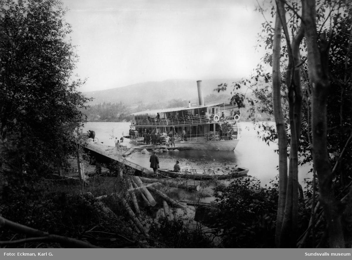 Hjulångaren Indalen har stannat vid Indals sågverk för av- och ilastning av passagerare och gods. En man har tydligen åkt med båten och haft cykeln med i båten. Ur Karl Eckmans glasnegativsamling.