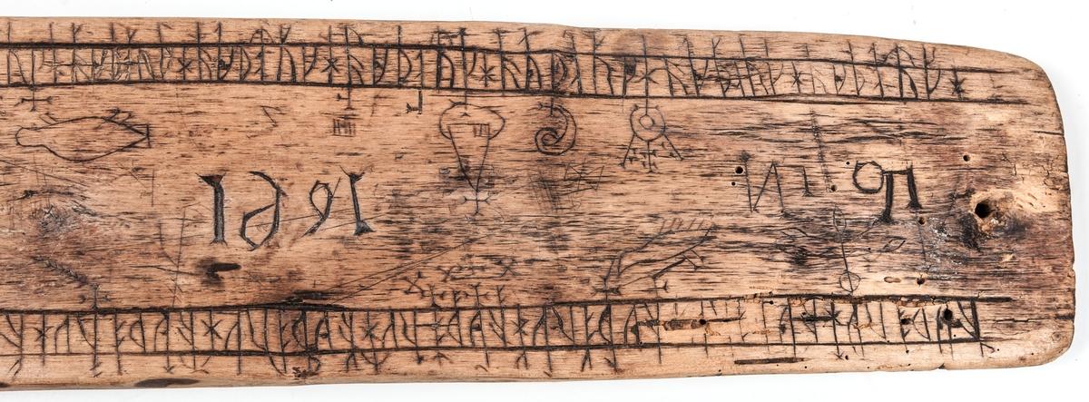 Runstav av trä, platt. längd 57 cm, bredd 9 cm. Märkt med initialer och 1691.