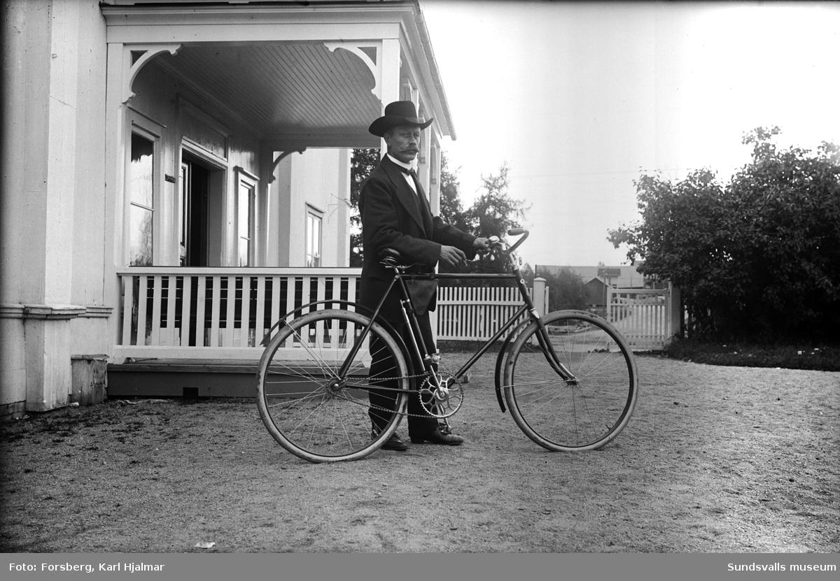 """Man med en cykel, ståendes vid en förstukvist. """"Kontorsbyggningen""""."""