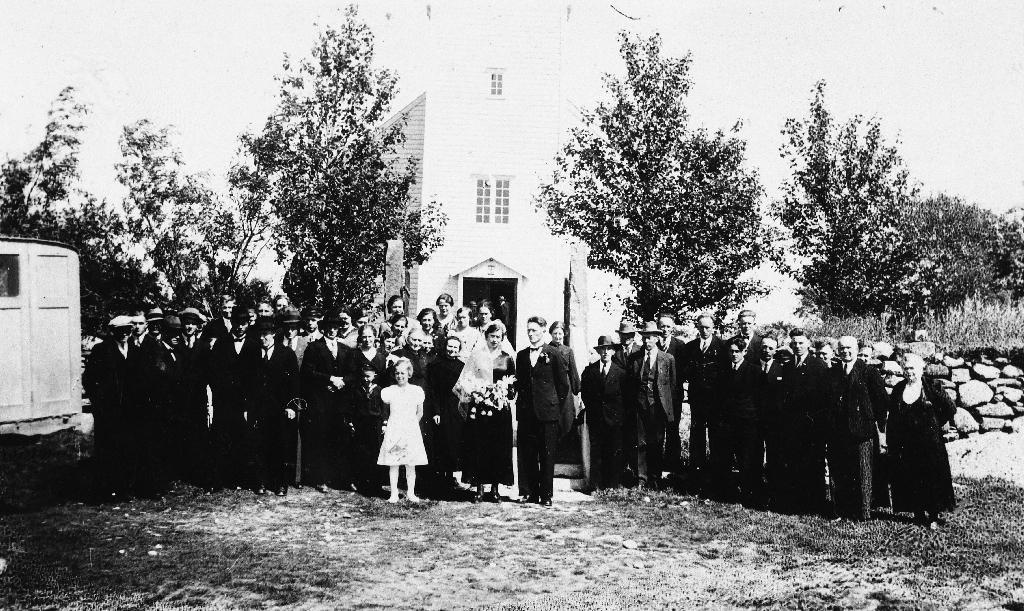 Brudeparet Kari f. Osland, Bjerkreim og Magne A. Undheim med bryllupsgjester framfor Time kyrkje i 1937. Dei budde på Vestly bnr. 1.
