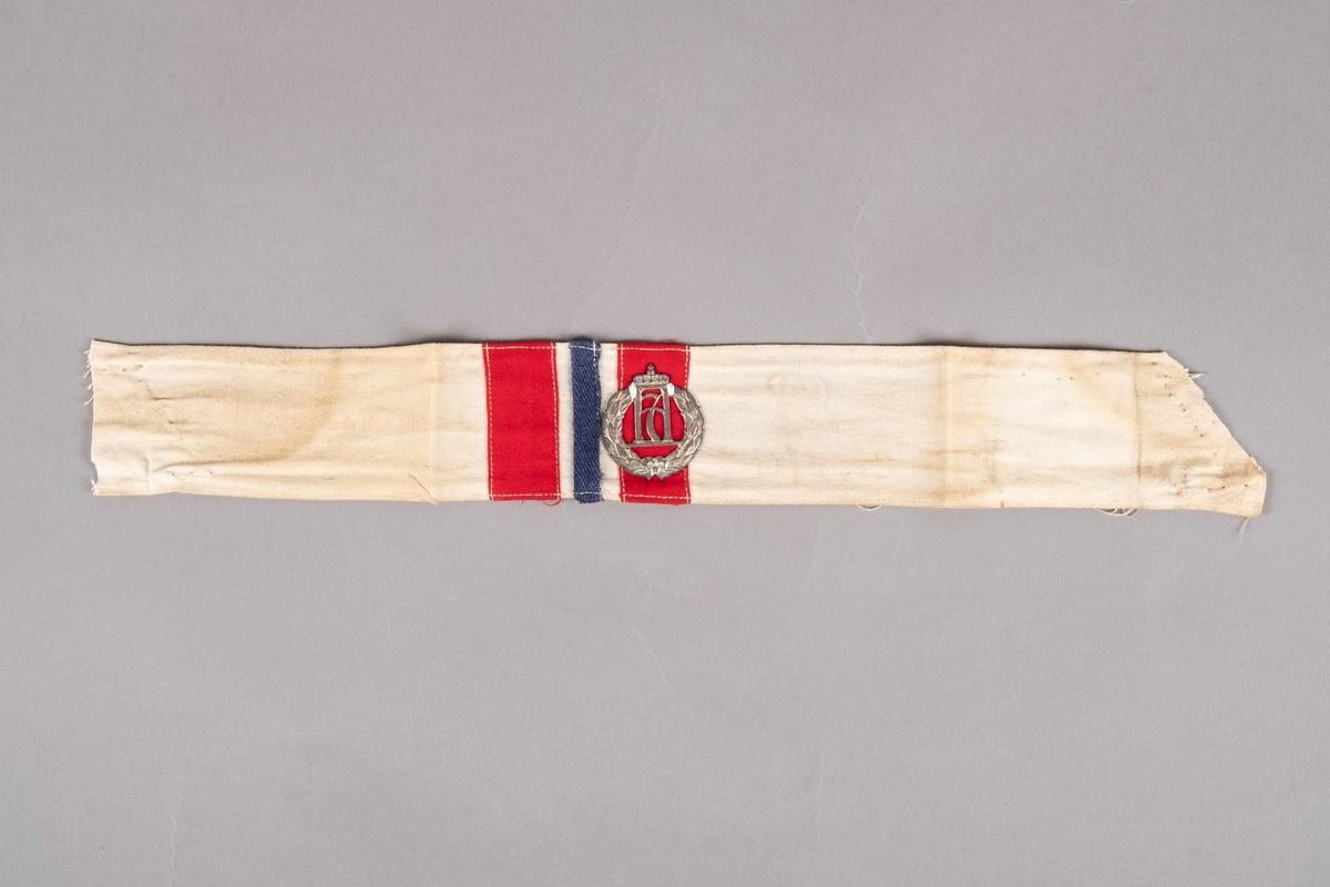 Et armbind i hvit bomull med påsydd rødt og blått tekstillapper. I midten er det påsydd Haakon 7. merke. Det er stempler på armbindet som er noe falmet.