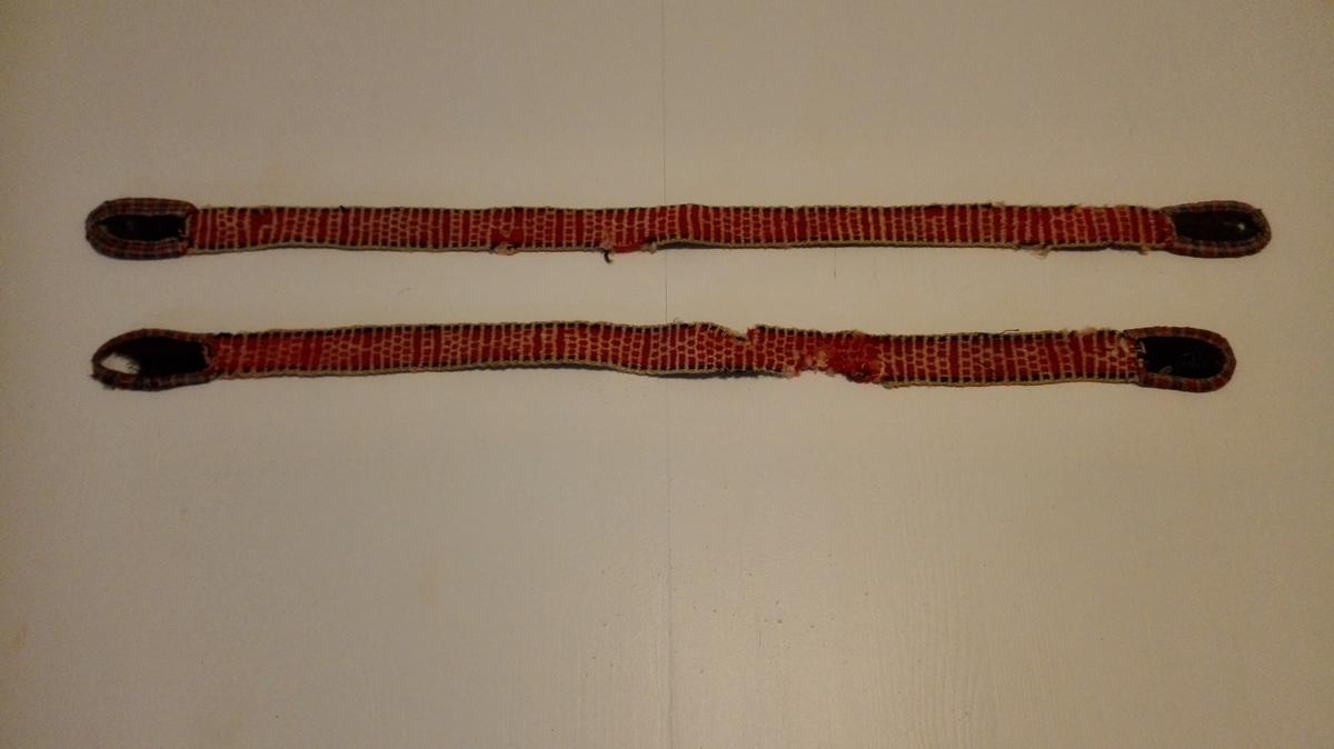 1 par buksesæler  Et par bukseseler vevet i mönster i båndgrind av rödt, hvidt og grönt ullgarn. Meget slitt og noe defekt, den ene er avslitt og sammensydd igjen og derfor kortere enn den annen. Længde 73,5 og 67 cm, bredde 2,7 cm. Stammer fra en auksjon i Laviksdalen.  Gave fra gårdbruker M.A. Ringereide, Lavik.