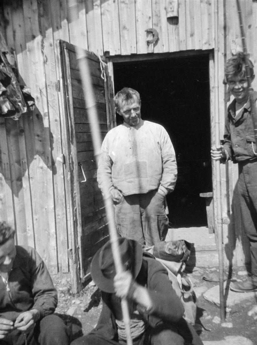 Fire menn utenfor ei hytte, antageligvis ved Revsjøen, Gausdal. En har ensfarget busserull. To av de har lange bambus fiskestenger, også kalt langbambus. På en av de synes snella.