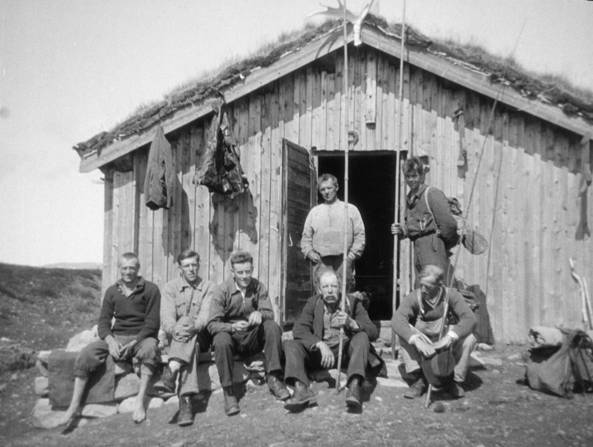 Sju menn utenfor hytte, antageligvis ved Revsjøen. Hytta har en hestesko festet som bakvendt C, og tre av de har lange bambus fiskestenger, kalt langbambus. Klær og en sokk henger på veggen og elgerevir på takmønet.