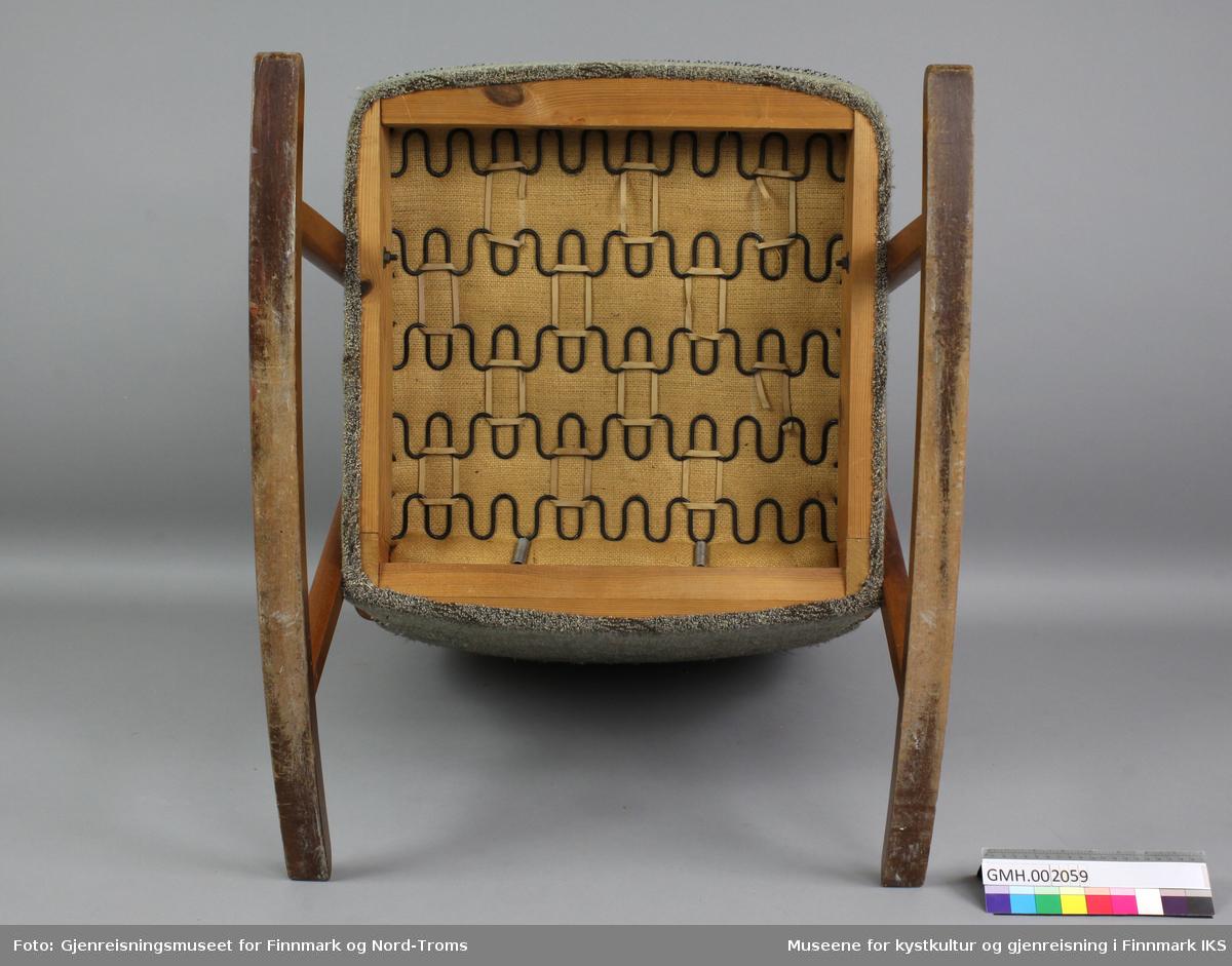 Gyngestolen har buede armlener i lakkert tre. Disse er forbundet med to ben som igjen er festet til meier. Stolen er trukket med lysegrønt mønstret stoff. Sitteflaten skiller seg ut gjennom bruk av rødt stoff med samme mønster som resten. Kantene er omkranset med et grått og svart kantbånd. Polstringa består av serpentinfjærer som er festet til ramma og til hverandre med gummibånd.