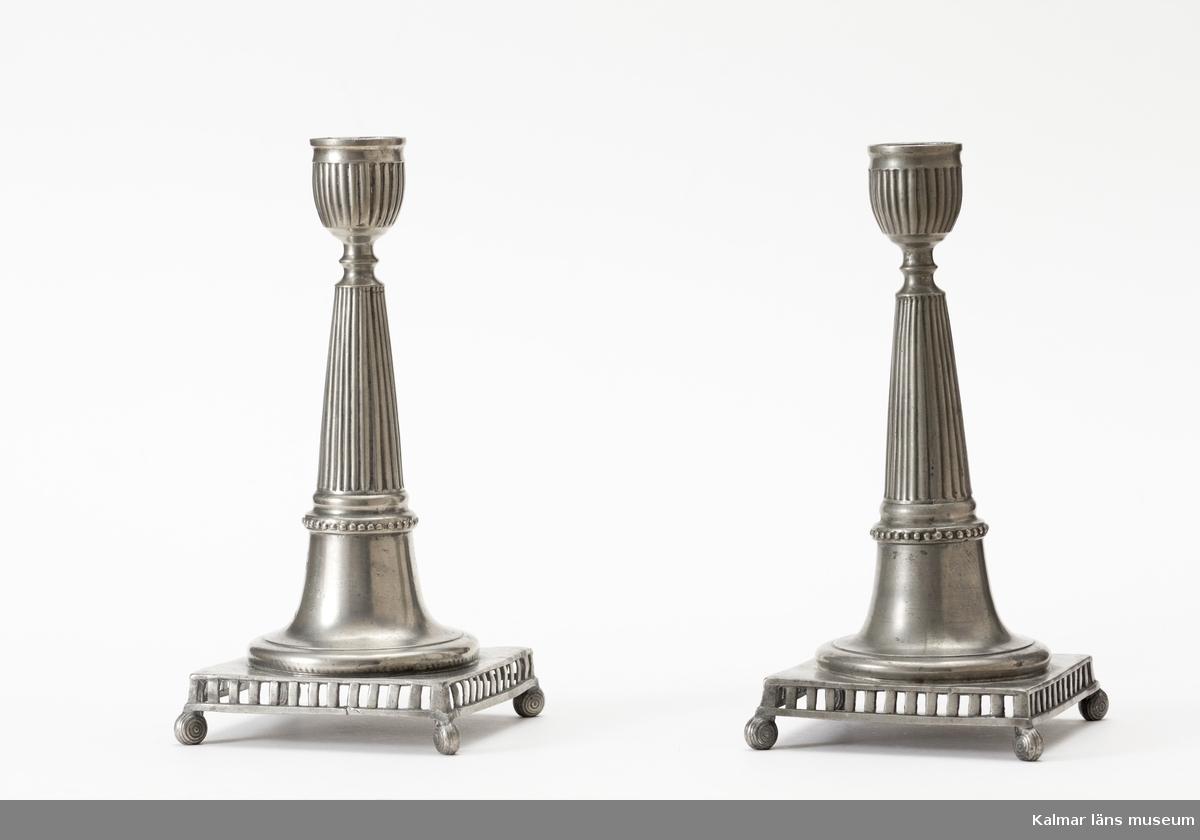 KLM 5650. Ljusstake, av tenn. Foten fyrsidig med genombrutna smala sidstycken vilande på fyra rundade små fötter. Skaftet runt, avsmalnande uppåt, räfflat. Ljushållaren räfflad. Hattens rand trubbtandad. Årsstämpel 3 C (1809), 2 mästarstämplar: JPF (Johan Petter Fagerström, 1798-1837), 2 stadsstämplar, 1 kontrollstämpel. En i ett par, hör samman med KLM 5651.
