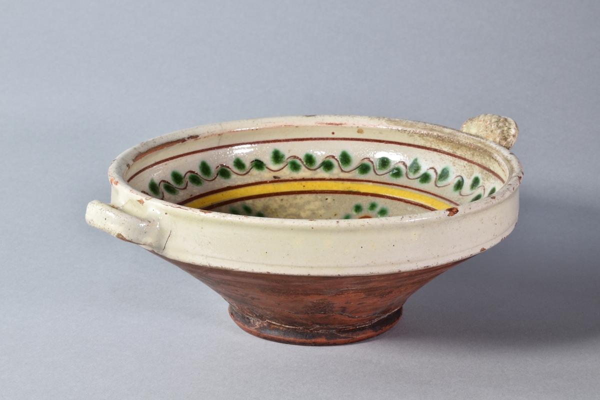 Skål av lergods, konisk. Engoberad och blyglaserad invändigt. Platt tumgrepp och ett öra på motstående sida.  Dekor i grönt, gult och brunt av våglinjer med prickar, rand och stiliserade blommor. I botten växtmotiv.