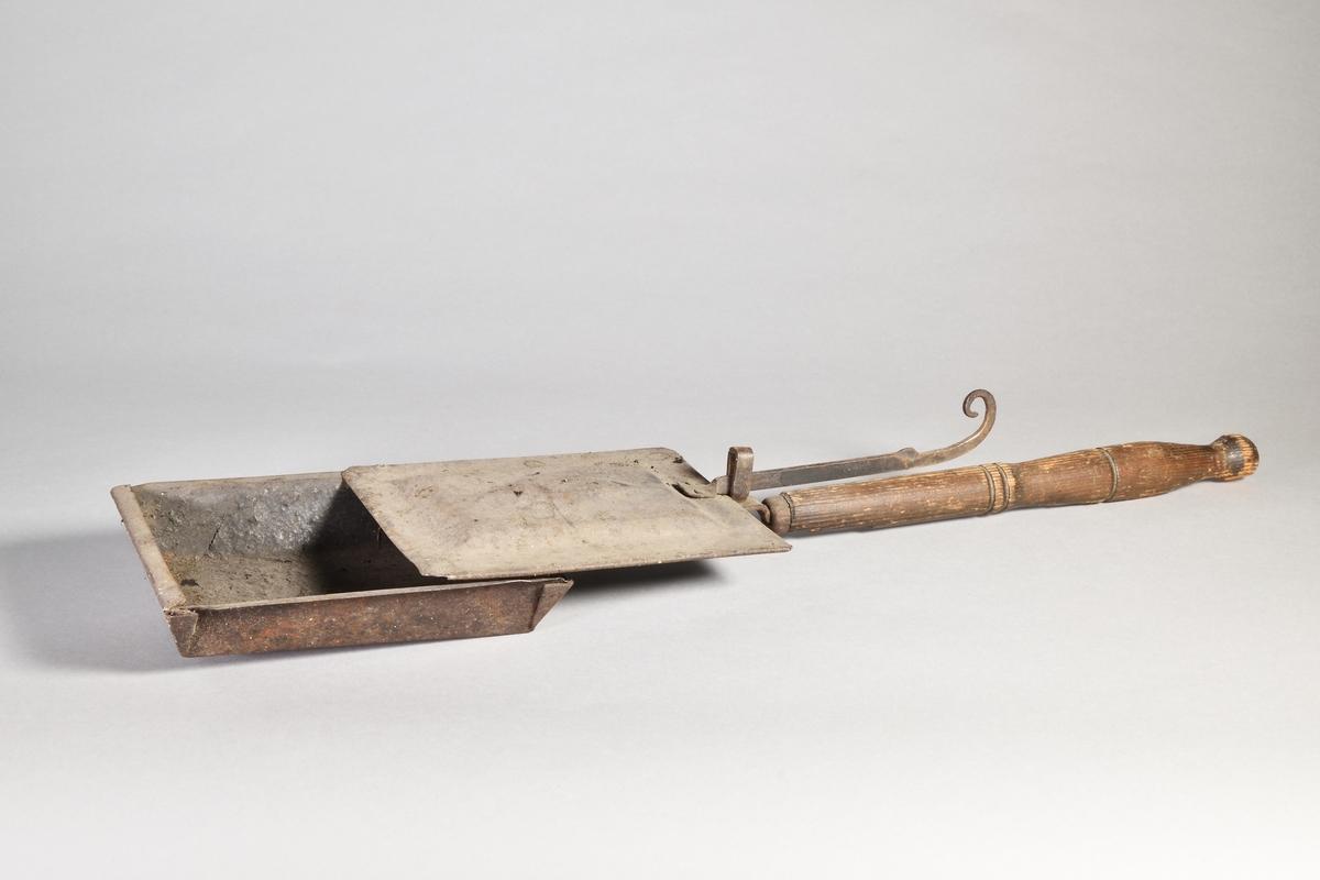 Kaffebrännare av järn, rektangulär, med skaft av trä. Brännarens lock har upphöjt mönster i form av en romb på en rektangel; lockets fäste avslutas i en smidd uppåtböjd krok. Skaftet avslutas med knopp.