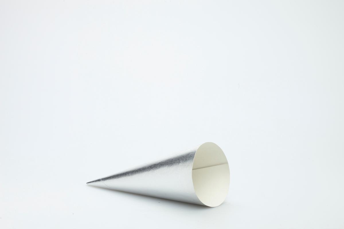 Kjegleformet iskrempapir (kremmerhus) i aluminium. Kremmerhuset er med farger på utsiden, og matt uten farge (hvit) på innsiden. Kjeglehuset er i ensfarget sølv. Ruglete papir.