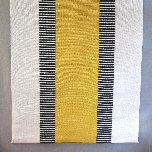 """Löpare, tre stycken, vävd i tuskaft och varptvist. Löparen har ett 130 mm brett enfärgat mittparti i blått, rött eller gult med ett 45 mm brett tvärrandigt tvistparti i svart och blekt på vardera sidan. Ytterkanten är blekt och 85 mm bred. Varpen är blekt, svart och färgat i tvåtrådigt bomullsgarn och inslaget i halvblekt lintow. Löparen med gult mittparti är 385 mm bred och 1095 mm lång, den röda är 380 mm bred och 1340 mm lång.  Den blå och den röda löparen är märkt med ett vitt bomullsband med texten: """"DANS"""" Ann-Mari Nilsson.  Löparen med modellnamn Dans är formgiven av Ann-Mari Nilsson och tillverkad av Länshemslöjden Skaraborg. Den finns med  på sidan 32-33 i vävboken Inredningsvävar av Ann-Mari Nilsson i samarbete med Länshemslöjden Skaraborg från 1987, ICA Bokförlag. Se även inv.nr. 0001-0011,0013-0040."""