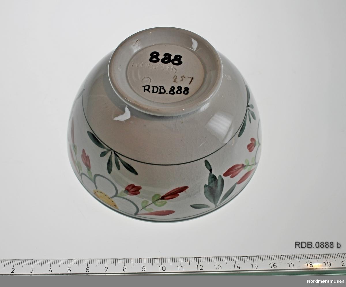 Liten bolle i steingods med lav stett. Kvit bunnfarge. 4 cm bred dekorbord med blomster og blad øverst på utsida.