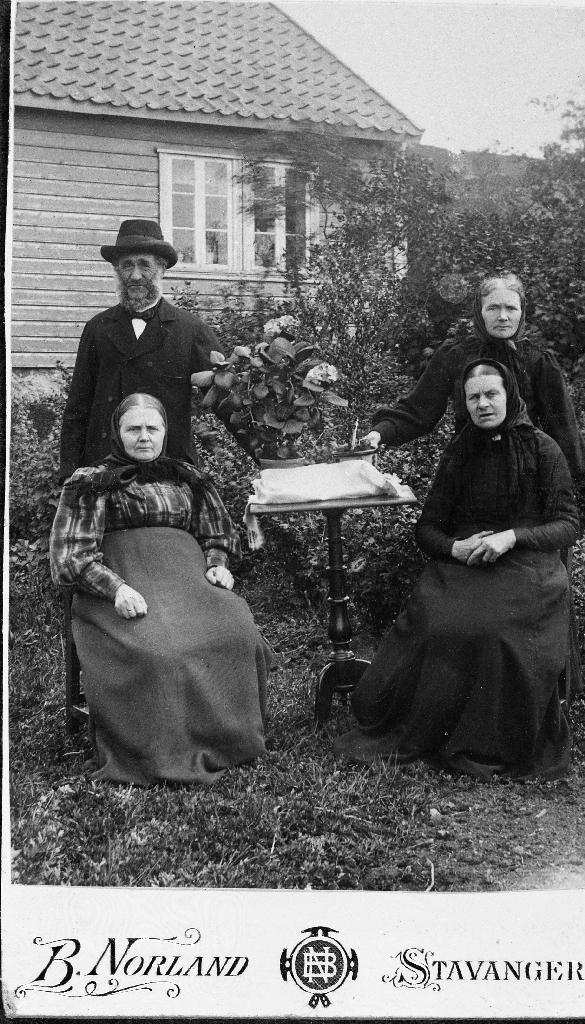 Vitjung i hagen hos Tønnes Nilson Kverneland (1840 - 1927)og Karen Nilsdtr. Kalberg (1848 - 1931) (bak). namnet til kvinna framme t. v. er ukjent, t. h. Birgitte Kalberg (1841 - )
