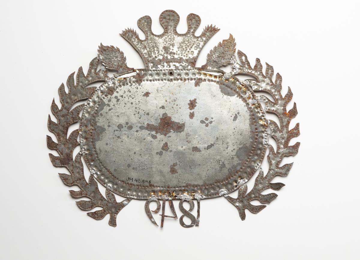 Kistplåt med oval plåt med klippta dekorationer runt omkring. Toppen är krönt av en kungakrona och längst ner har man daterat plåten 1849. Texten är svår att läsa.
