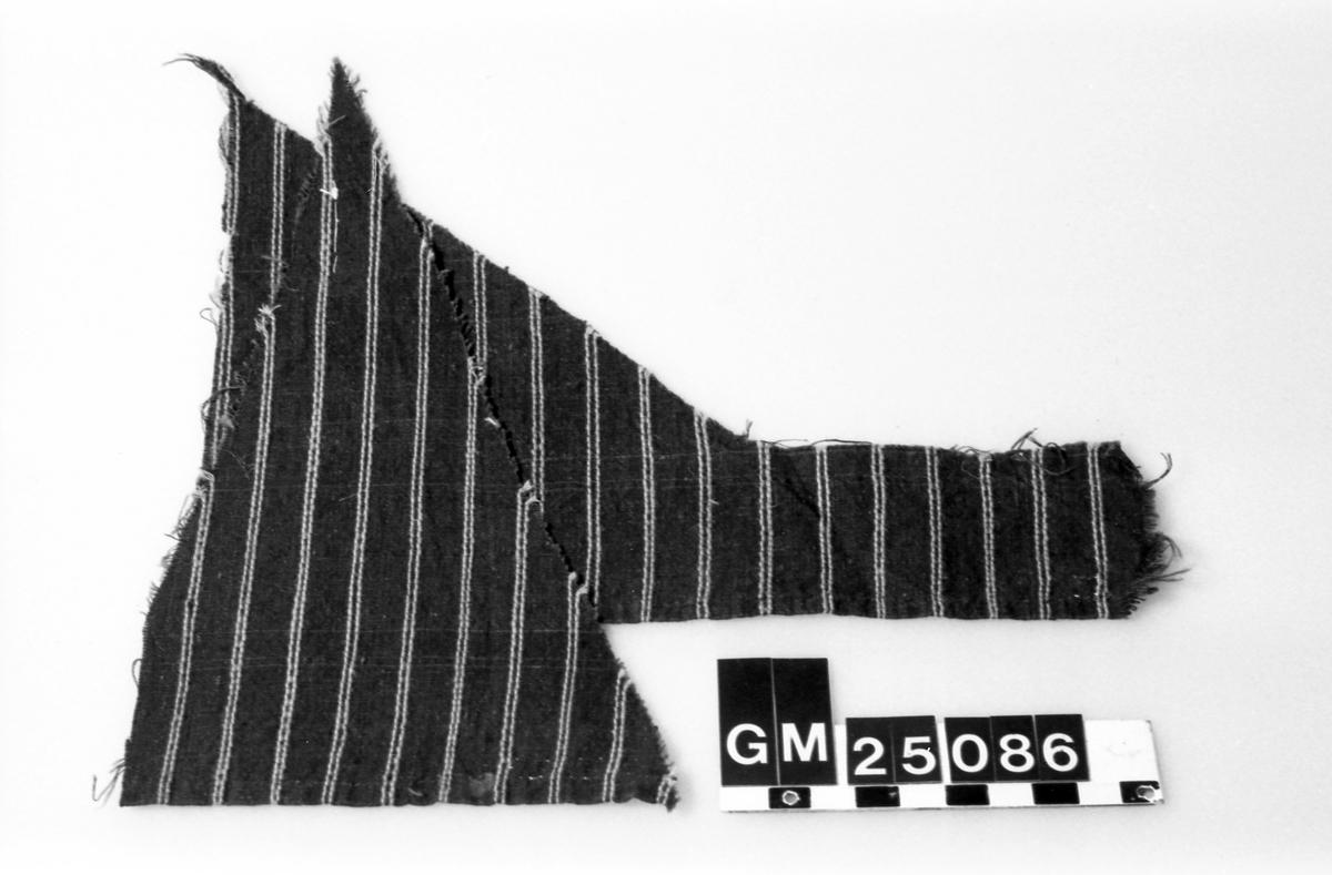 Två tygfragment. Två stycken av samma tyg, bägge fållade 0,5 cm med svart tråd , enkel vikning vid stadkant. Ränder i inslagsriktning, tuskaft. Bomull i varp och inslag, dubbla ljusblå ränder i inslagsrips på mörkblå botten. Eventuellt nederdelen av ett förkläde.