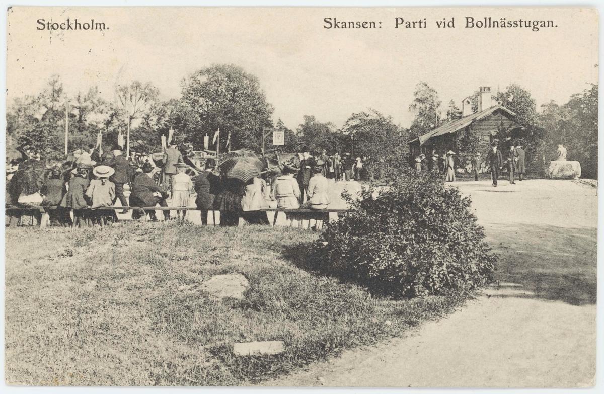 """Vykort med motiv från Skansen. """"Parti vid Bollnässtugan"""". Besökare på en bänk."""