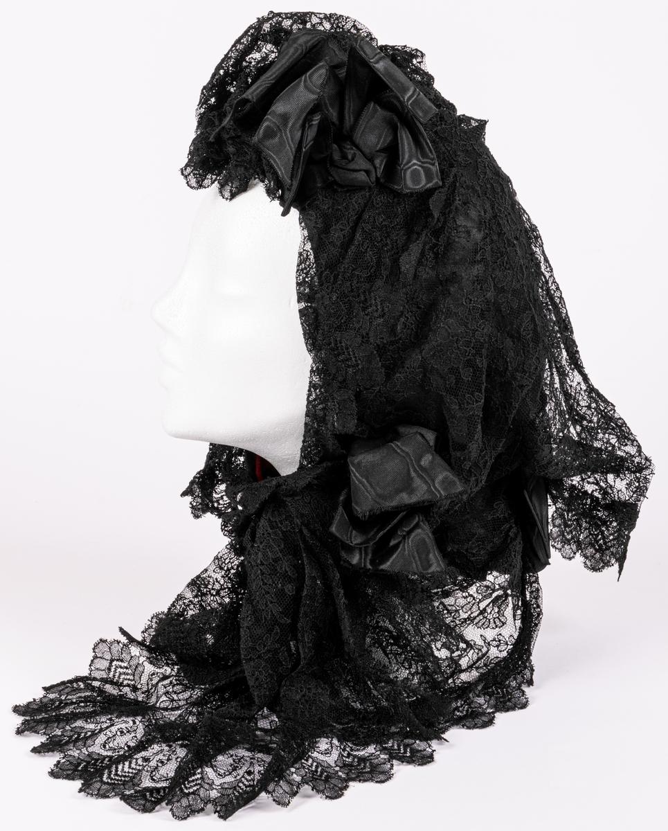 Aftonhätta av svarta spetsar och moiréband.