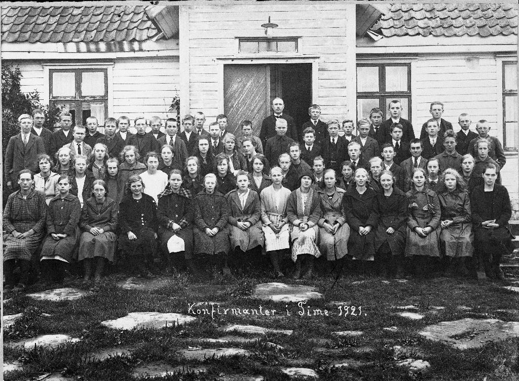 Konfirmantar i Time i 1921 framfor klokkargarden. Presten Helle står bak i døra.