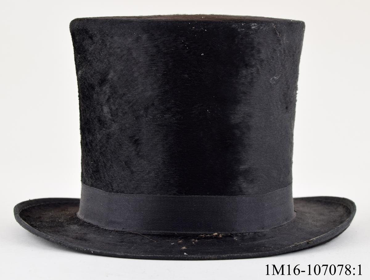 Cylinderhatt i svart sammet med tillhörande hattask. Hattens insida är fodrad med två postkvitton och ett brev. Tillverkare: S. Rothenborg & co, Göteborg. Föremålen har tidigare märkning BT 141, som är hembygdsföreningens (broddetorps hembygdsförening). Hatten med ask fanns och har förvarats i Bankastuga, Hornborga.