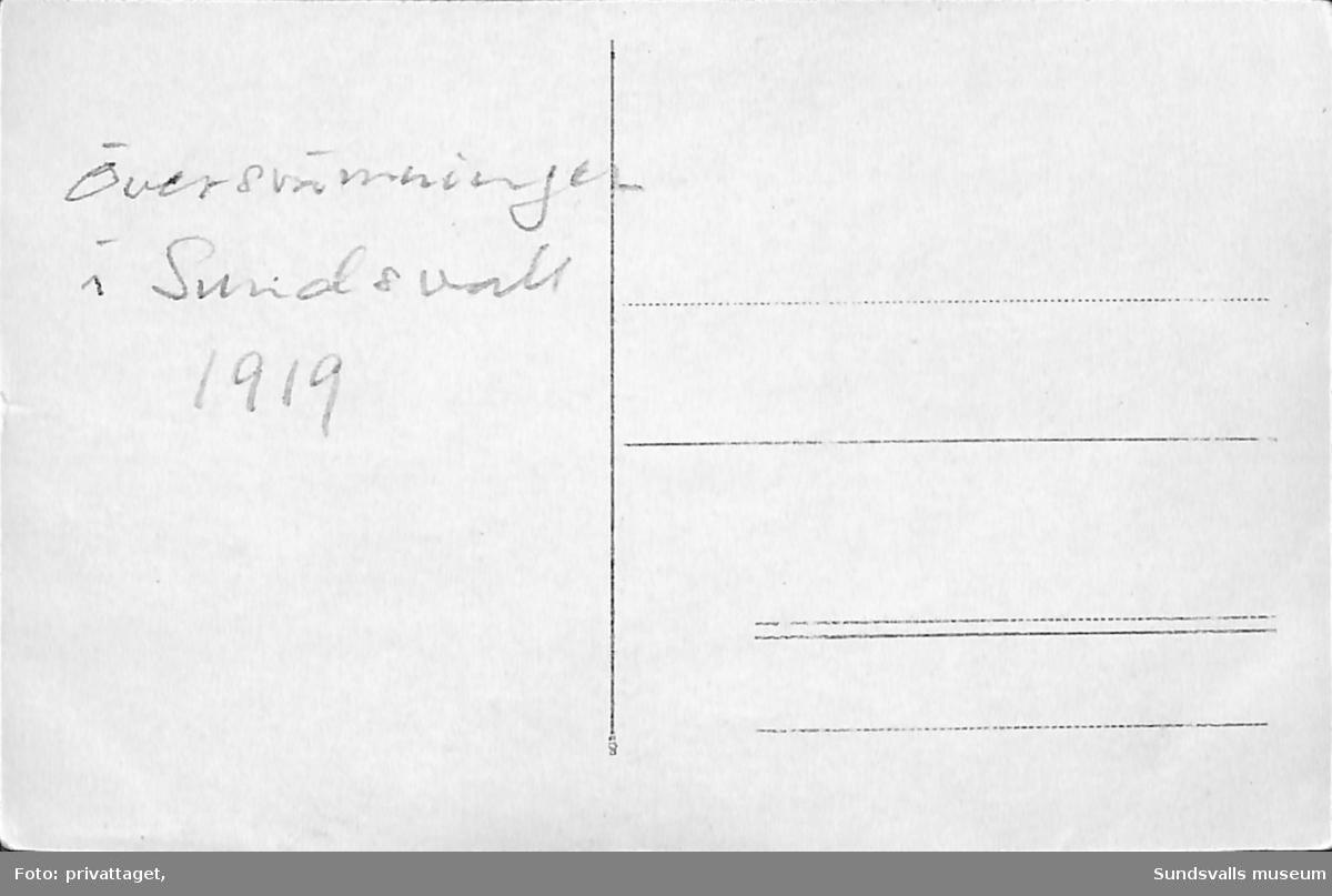 Vykort med motiv av ett vattendrag som svämmat över. Text på baksidan: Översvämningen i Sundsvall 1919.