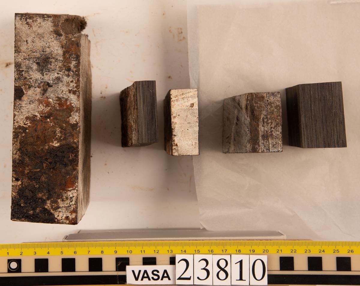 Del av bordläggningsplanka. Fyndnummer 23810 innehas av 5 bitar p.g.a. tidigare provtagning. Den största biten har ett borrspår.