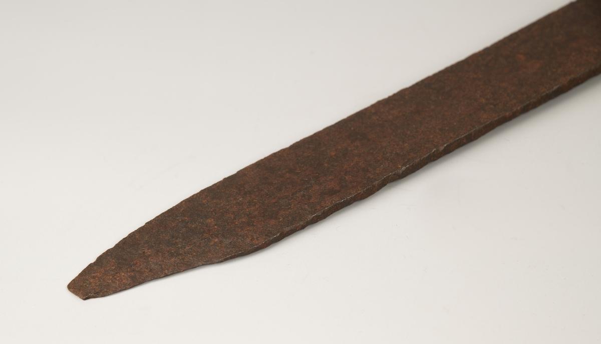 Sver med bredt bladt som er tilspisset ytterst. Grovt rettskåret håndtak med et jernbånd fra toppen av skaftet og tverssover overgangen mellom  blad og skaft.