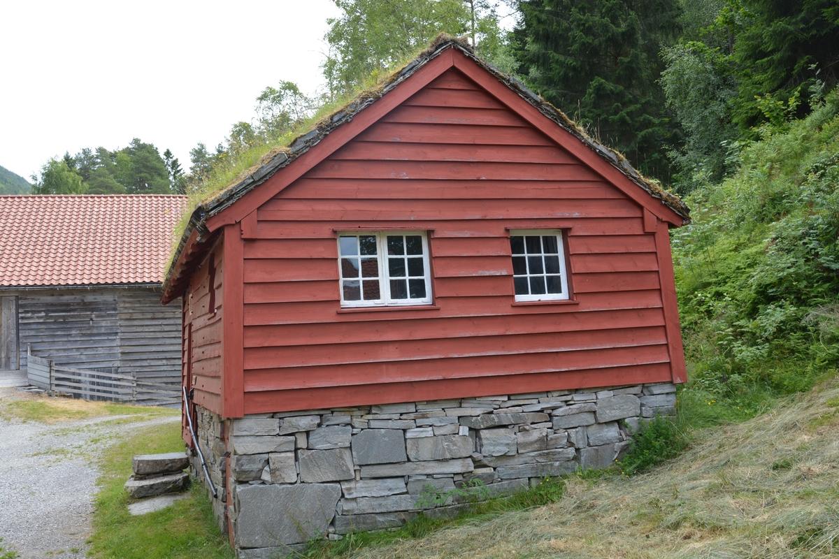 """Bygning med to rom: """"eldhus"""" / """"utdør"""" i reisverk og sjølve stoverommet i laft. Grue i eldhusdelen.  Liggande panel utvending, med unntak av eit stykke på eine langveggen som har ståande panel.  Raudmåla. Torvtak"""