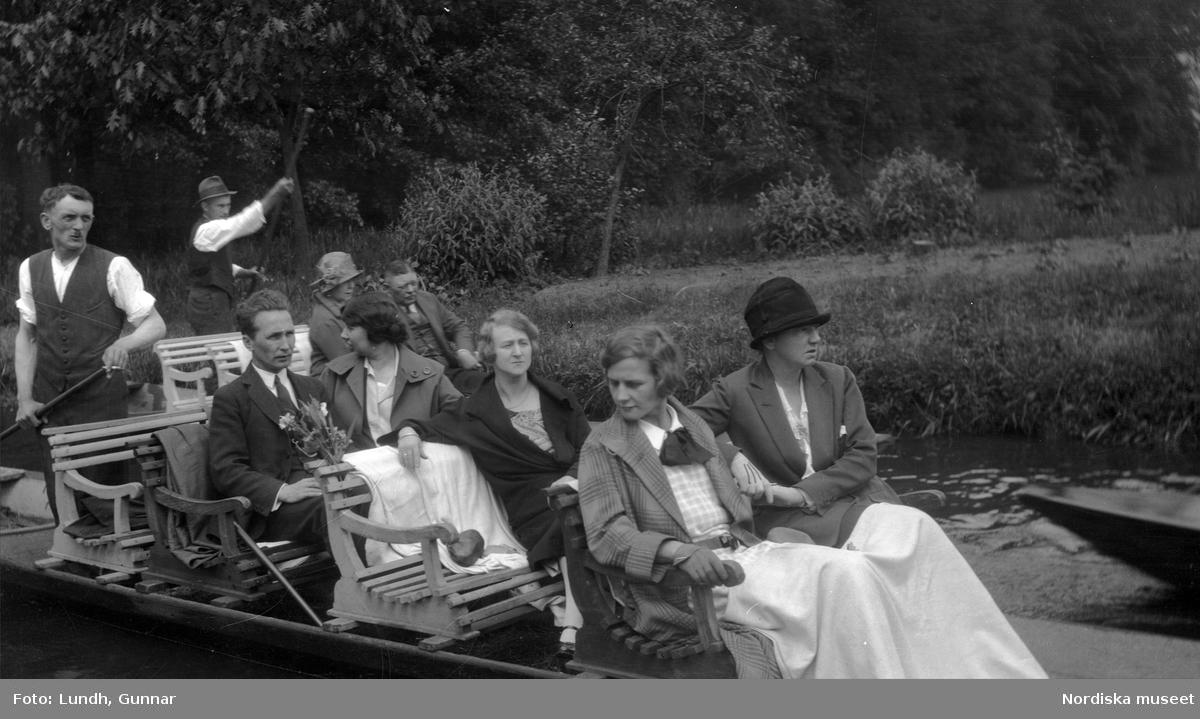 Motiv: Utlandet, Spreewald 92 - 101 ; Kvinnor och män sitter i en båt, två kvinnor i folkdräkt. två kvinnor i folkdräkt står vid ett hus.