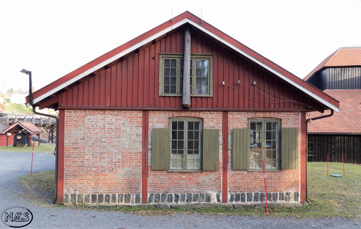 Produksjonslokale. Antas å være fra 1870/ 80 - årene. Langstrakt bygg med utmurt bindingsverk. Lange vindusrekker og saltak. Innvendig er det fortsatt spor etter fra tidligere bruk med drivakslinger i taket og et eget metalurgisk laboratorium.