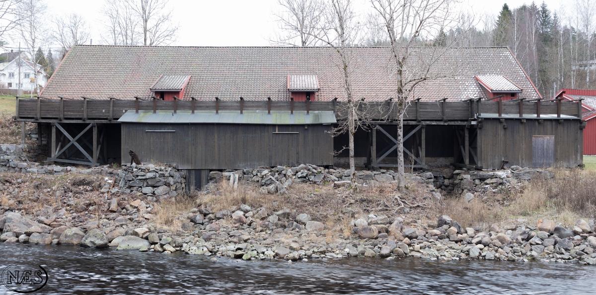 Hammeren. Stor rektangulær bygning. Bestående av ett stort rom. Grunnmuren er oppført delvis i nyere betong og delvis med naturstein. Bakveggen mot terrenget består av store grove naturstein i bunn og avsluttes med slaggstein mot toppen. Veggene er utvendig panelt med tømmermannskledning. Inngang gjennom dobbel labank-dør på kortside mot sør og langside mot øst. Vinduer på en langside. På langside mot vest og elven har bygget en vannrenne, som drev vannhjulene. Bygget er reist med saltak og tekket med rød teglstein.