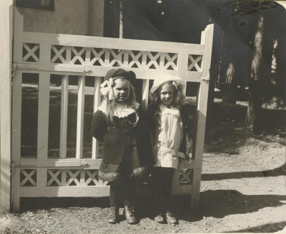 Porträtt av två flickor vid grinden.