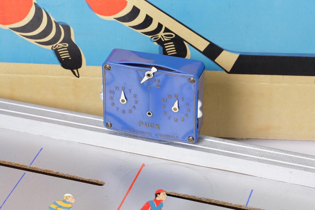 Ishockeyspel tillverkat av hård träfiberplatta, med profilerade sargar av plywood. Lackerat i silverfärg med röda markeringar. Det har tio spelare av plåt samt två målvakter. Spelarna och målvakterna sköts med metallstänger från spelets kortsidor. Vid  varje mål finns en signallampa. På ena långsidan finns ett batteridrivet matchur, infattat i ett blått plasthölje.  Pucken är tillverkad av svart plast.  Spelet förvaras i originalkartongen, som är gjord av ljus wellpapp. Den har ett färgtryck på framsidan föreställande  en ishockeyspelare.