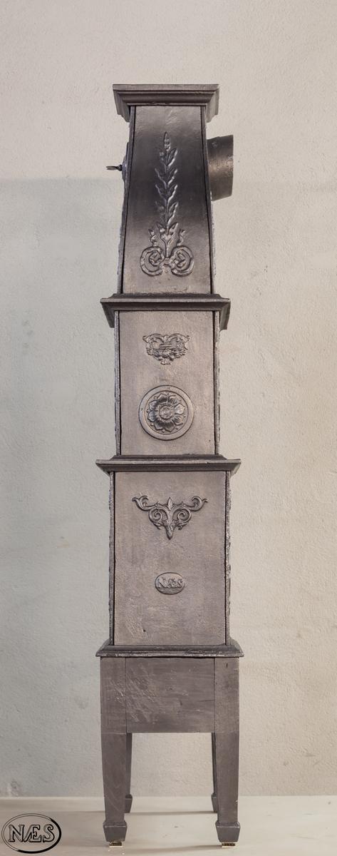 Ovn i  to etasjer med svunget topp. Ovnsdør på kortside og med innskrift på motsatt kortside. Langsidene i 1. og 2. etg er symmestrisk bygd opp med lik ornamentikk, foruten at på langside 1 er en griff i glatt oval medaljong, mens langside 2 har rundbuet åpning. Ovnen avsluttes med en svunget topp.