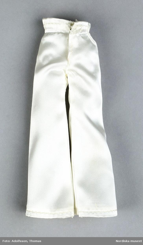 a) Manlig docka med ljusbrunt, formpressat hår, skägg och mustasch. Påmålade blå ögon. Klädd i b) vita utsvängda långbyxor och c) guldbrun jacka av glansigt syntetmaterial. Stor krage och guldfärgade knappar på jackan. d) Blå scarf med enkel knut kring halsen. Gummiresår i midjan samt tryckknapp av metall. e:1-2) Vita skor av plast.