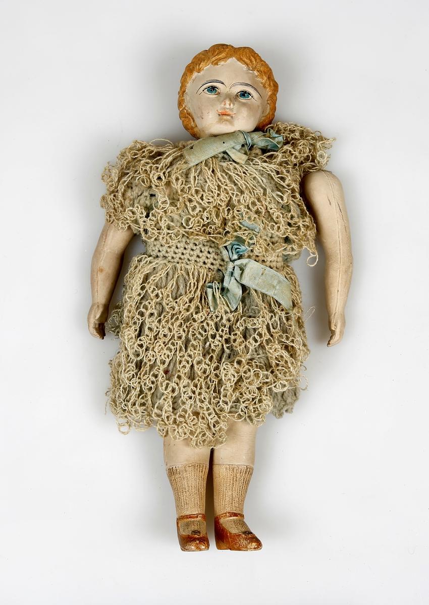 Dukke med plastkropp og -kode. Hode og armer er festet til resten av kroppen. En arm er løs. Dukken har heklet kjole.