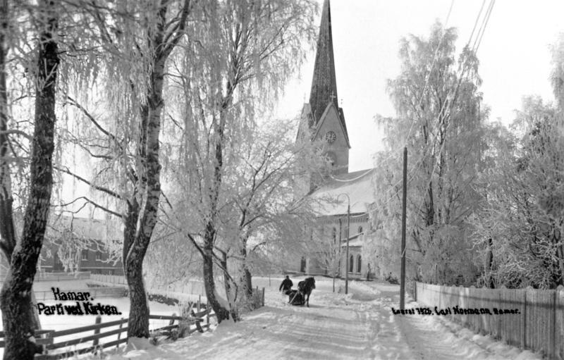 Svart-hvitt foto av rimete bjørketrær som leder ned mot Hamar Domkirke, og en hest med slede rett foran kirken. (Foto/Photo)