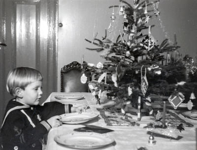 Svart-hvitt foto av en liten gutt i matrosdress som dekker bordet. På bordet står også et lite juletre.. Foto/Photo
